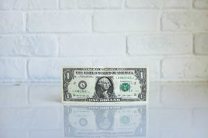 U.S. dollar in front of a white brick wall