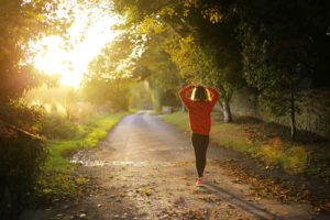 woman walking down path representing a healthy lifestyle and healthy financial planning
